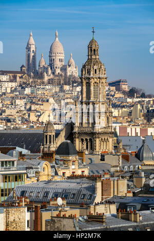 Rooftops of Paris with the Sacre Coeur Basilica in Montmartre and Trinity Church. 18th Arrondissement, Paris, France - Stock Photo