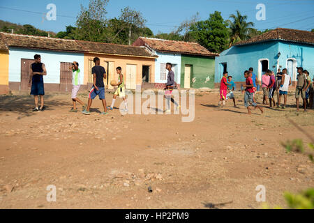 A group of young Cuban boys playing football on a rough ground football pitch in Trinidad Cuba with traditional - Stock Photo