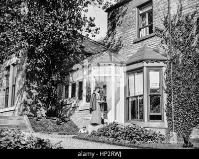 A young Edwardian lady, with a dog at her feet, wearing a long dress, cape and small hat standing outside a house - Stock Photo