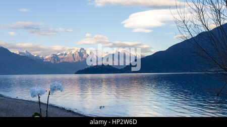 Pianello del Lario, Como - Italy: Evening light at Lake Como with snow-capped mountains and cloudy particular conformations - Stock Photo