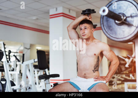 Beautiful athletic bodybuilder guy, carries out exercises with d - Stock Photo