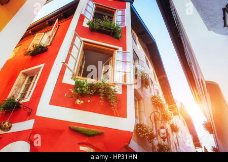 Typical Austrian Alpine house with bright flowers on the balcony - Stock Photo