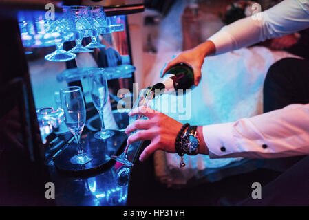 waiter pours champagne into glass - Stock Photo