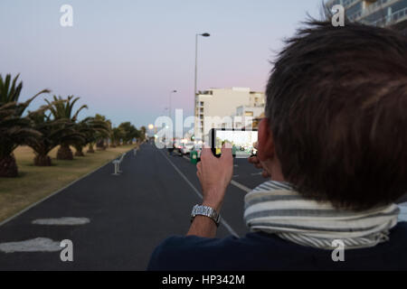 Cape Town, South Africa - November 14, 2016: A Caucasian middle aged man is filming the supermoon in Cape Town, - Stock Photo