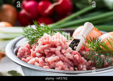 Raw ground meat in white bowl. Minced pork on a background of fresh organic vegetables - Stock Photo