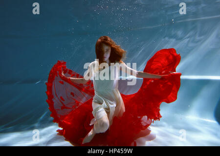 Underwater in the pool with the purest water. Beautiful young girl in a scarlet dress and flowing hair. - Stock Photo