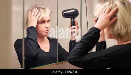 Mature woman used hair dryer in bathroom - Stock Photo