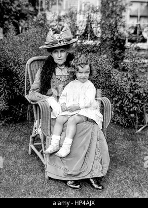 An older Edwardian lady sits in the garden in a wicker chair with a small child on her knee. The lady is wearing - Stock Photo
