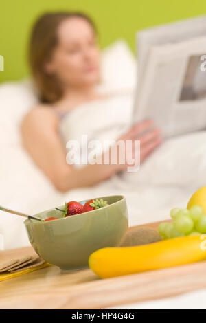 Model released , Junge Frau, 25+, mit Zeitung und Fruehstueck am Bett - woman with newspaper and breakfast in bed - Stock Photo