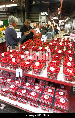 dealer sells fresh israeli strawberries infront of his shop at carmel market, tel aviv, israel - Stock Photo