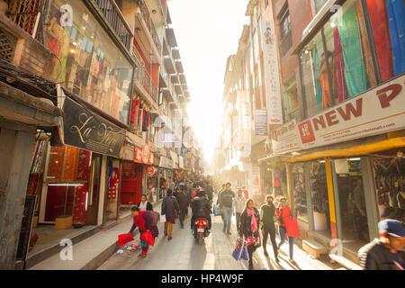 KATHMANDU, NEPAL - 16 December 2016: Shoppers walk through a busy street in the afternoon sunlight, 16 December - Stock Photo