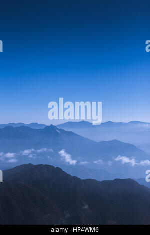 Sun and clouds over Himalayan foothills (Kanchanjungha Himal), eastern Nepal - Stock Photo