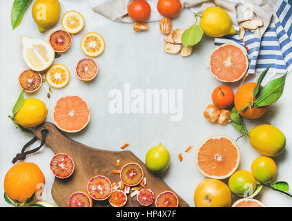Natural fresh citrus fruits on wooden rustic board over grey marble table background, top view, copy space - Stock Photo