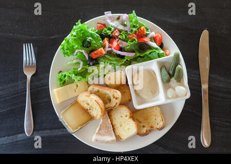 A French chesse plate with Tomme, Belkot, and Saint Marcellin cheeses, salad, dijon mustard, pickles, and shallots - Stock Photo