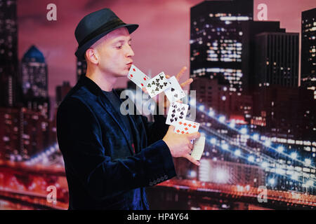 Portrait juggler magician is interesting black suit with cards i - Stock Photo