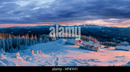 Fantastic sunset over snow-capped mountains and wooden chalets.  - Stock Photo