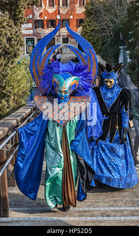 Venice,Italy-February 18, 2012: Two unidentified persons disguised in blue costumes walking on the Academia Bridge - Stock Photo