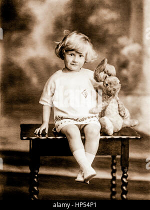 Formal Edwardian portrait of a small child sitting on a low table, wearing a knitted dress and cuddling her toy - Stock Photo