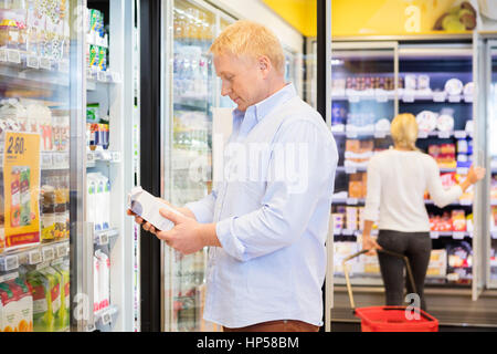 Man Holding Juice Packet In Grocery Store - Stock Photo
