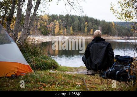 Male Backpacker Enjoying The View Of Lake At Campsite - Stock Photo