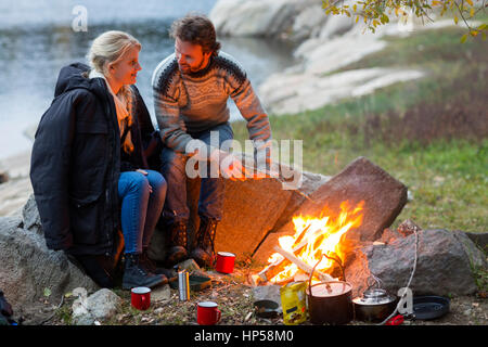 Couple Looking At Each Other White Sitting By Campfire - Stock Photo