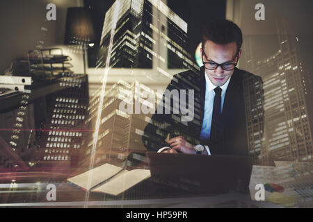 Optimistic businessman working on laptop at office in the night, Working overtime with big city in background - Stock Photo