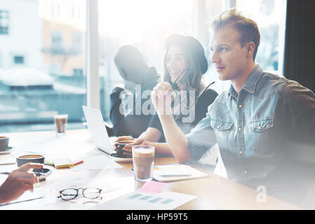 Young people talking in cafe or office, handsome man and pretty girl in casual wear having conversation with colleagues, - Stock Photo