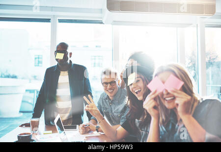 Beautiful young people having fun with sticky notes sitting together at cafe table near bright window, playing name - Stock Photo