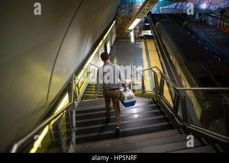 Buenos Aires, Argentina. 18th Feb, 2017. A man carries his little dog in a kennel, while walking downstairs to board - Stock Photo