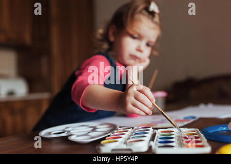 Cute happy little girl, adorable preschooler, painting with wate - Stock Photo