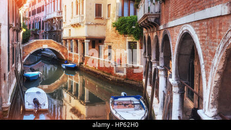 Traditional Gondolas on narrow canal between colorful historic houses in Venice Italy - Stock Photo