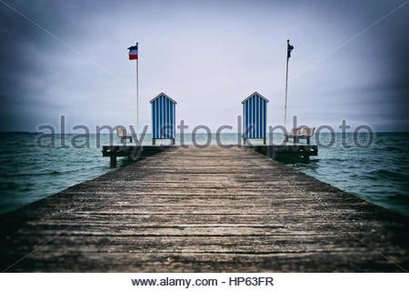 Pier jetty ocean changing cabins blue stripped - Stock Photo