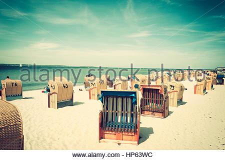 In a row hooded beach chairs sunshine sand seaside - Stock Photo