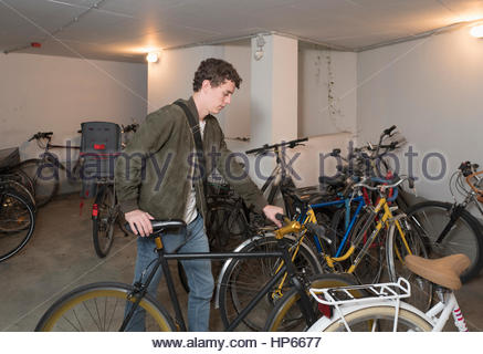 Young man parking fixie bicycle Hipster garage - Stock Photo