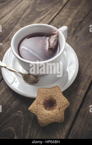 Fresh cookie with fruit jelly and tea cup  over rustic wooden background - Stock Photo