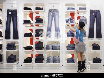 Junge Frau steht vor Regal einer Boutique (model-released) - Stock Photo