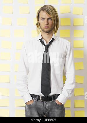 Junger Mann steht in Hemd und Krawatte vor Postit-Wand (model-released)