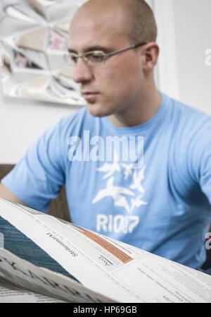 Mann liest zu Hause Stellenanzeigen in Zeitung (model-released) - Stock Photo