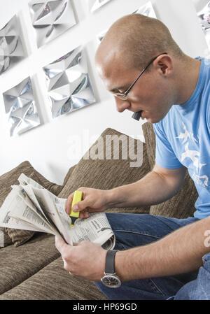 Mann markiert zu Hause Stellenanzeigen in Zeitung (model-released) - Stock Photo