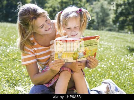Mutter sitzt mit Tochter auf Wiese, lesen Buch (model-released) - Stock Photo