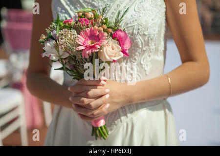 Woman holds small pink bouquet in hands - Stock Photo