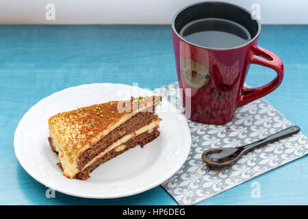 Cake piece with coffee in red cup on turquoise table - Stock Photo