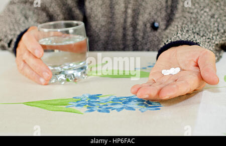 Elderly hand holding a glass of water and pills - Stock Photo