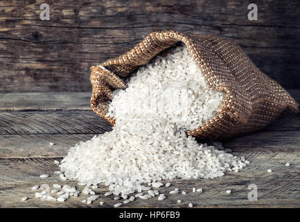rice on wooden background. Scattered grains of white rice on wooden background - Stock Photo