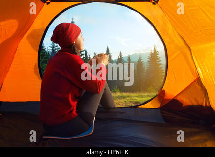 View from inside a tent on mountains landscape. Camping concept. Sunset inside a tent. Young woman sitting in the - Stock Photo