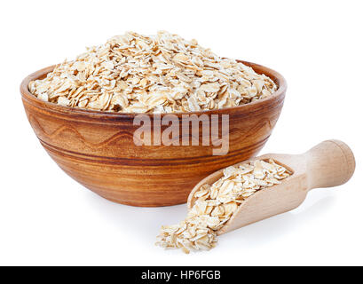 Oat flakes in clay bowl and wooden scoop isolated on a white background. Healthy food. Healthy groats. Ceramic bowl - Stock Photo