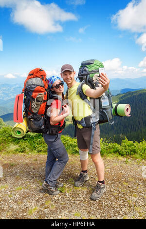 Couple of hikers taking selfie with mountains view on the background. Couple tourists woman and man make selfie - Stock Photo