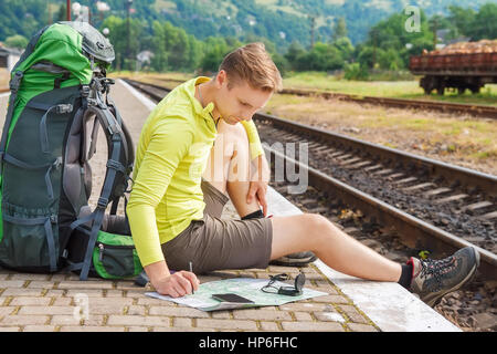 man sitting with map and travel bag at the train station. Traveler holding map, waiting for a train at train station - Stock Photo