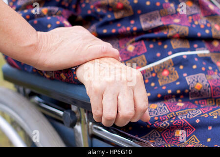 Handicapped elderly woman sitting in a wheelchair - Stock Photo