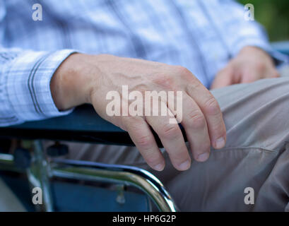 Handicapped elderly man sitting in a wheelchair - Stock Photo